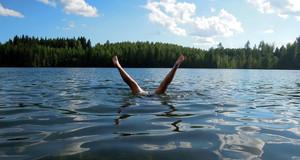 Aus einem See ragen zwei Beine aus dem Wasser, weil jemand unter Wassere einen Kopfstand macht.