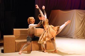 Bild wird vergrößert: Ein Tänzer sitzt auf Pappkartons und hält eine Tänzerin die vor ihm steht.