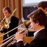 Nahaufnahme einer Gruppe junger Herren, die allesamt Trompete spielen.
