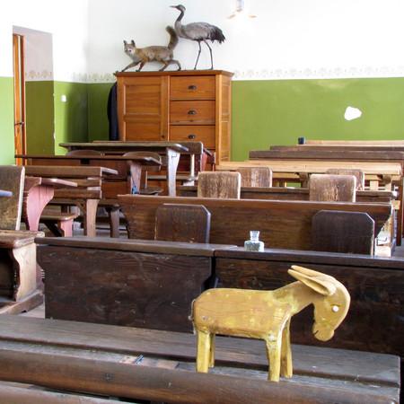Blick in das Klassenzimmer Volksschule um 1900. Im Vordergrund die so genannte Eselsbank zur Bestrfung von Schülern.