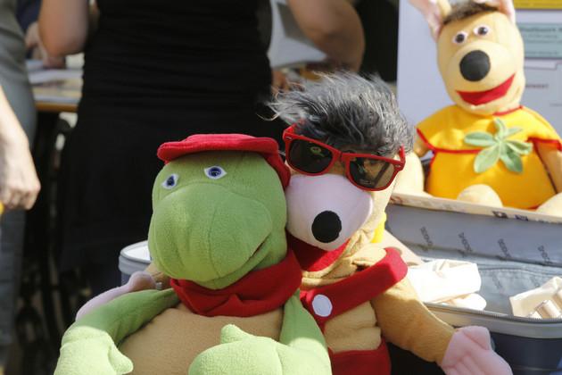 Auf dem Foto sind drei Handpuppen des kleinen Löwen und seiner Freunde zu sehen. Sie gehören zum Lernkoffer des Behindertenverbandes Leipzig e. V. Schildkröte Eddy und Maulwurf Brailli umarmen sich. Im Hintergrund sitzt das Hasenmädchen Lisa.