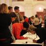 An einem langen Tisch drängen sich zahlreiche Menschen, um sich in Teilnehmerlisten einzutragen.