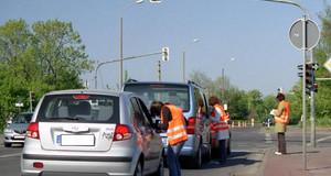 Befrager stellen Autofahrern an einer roten Ampel Fragen zu ihrer Verkehrsnutzung