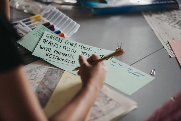 Frauenhand, die etwas auf grüne Moderationskarten schreibt