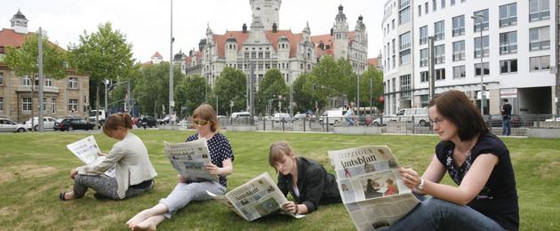 Vier Menschen lesen auf einer Wiese Amtsblatt. Im Hintergrund ist das Neue Rathaus.