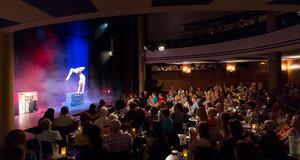 Akrobat bei einer Vorstellung im Krystallpalast Varieté. Viele Zuschauer sehen zu.