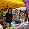 Zwei Frauen stehen an einem Bücherstand im Park in einem Pavillon.