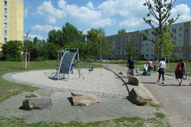Generationenpark Schönefeld Grünfläche mit Spielgeräten. Im Hintergrund sind Plattenbauten sichtbar.