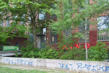"""Bild wird vergrößert: Eine niedrige Betonmauer mit Graffiti besprüht, im Hintergrund ein Backsteinhaus mit großem Schriftzug """"Kino"""", halb von Bäumen verdeckt"""