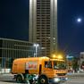Eine Reinigungsfahrzeug für Straßen reinigt eine Straße vor dem Wintergartenhochhaus
