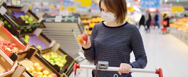 Eine Frau hat eine Maske auf und ist einkaufen. Sie legt einen Apfel in den Einkaufswagen.