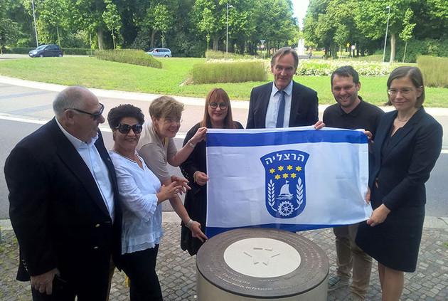 Sieben Personen halten die Flagge von Herzliya.
