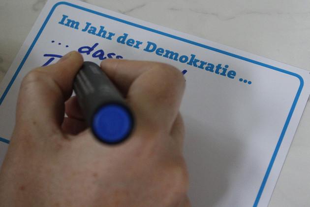 Detailaufnahme einer Hand, die eine Postkarte zum Jahr der Demokratie ausfüllt