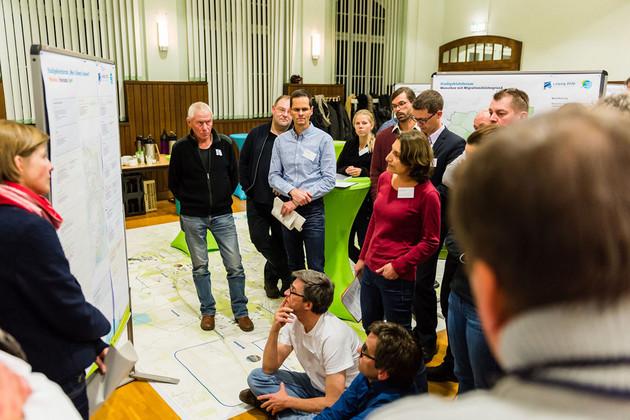 Eine Gruppe von Menschen diskutiert vor einer Moderationswand, zwei Menschen sitzen am Boden.