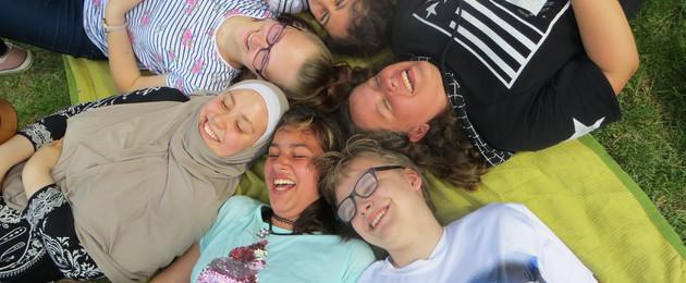Mehrere Kinder liegen auf einer Wiese im Kreis so dass ihre Köpfe zusammenliegen