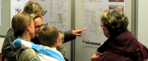 Menschen diskutieren vor einem Bebauungsplan