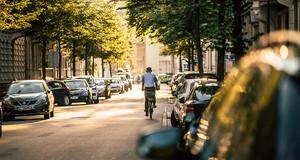 Fahrradfahrer mit Kopfhörern fährt auf einer Straße im Waldstraßenviertel. An den Seiten parken viele Autos.