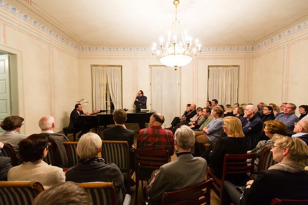 Ein Pianist am Flügel im Konzertsalon des Schumann-Hauses mit bunt verzierten Wänden und einem Kronleuchter. Um ihn herum Publikum auf Stühlen