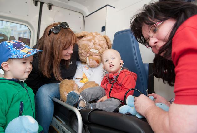 Ein kleines Kind hat ein Stetoskop in den Ohren. Eine Frau hört damit ein blaues Kuscheltier ab. Eine andere Frau und ein Junge sehen zu.