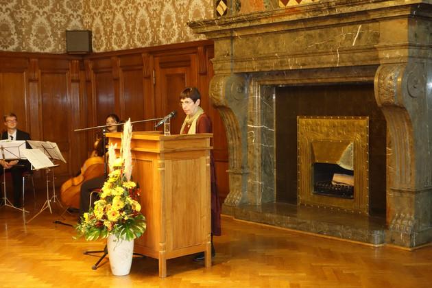 Dr. Heide Steer steht hinter einem Stehpult und redet. Vor dem Pult steht ein hoher Blumenstrauß