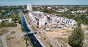 Von oben sieht man Neubauten, teilweise noch im Bau, entlang eines Wasserlaufes auf dem Paddelboote schwimmen