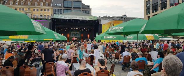 Stadtfest mit vielen Menschen, die an Tischen sitzen und sich das Programm auf der großen Bühne ansehen.