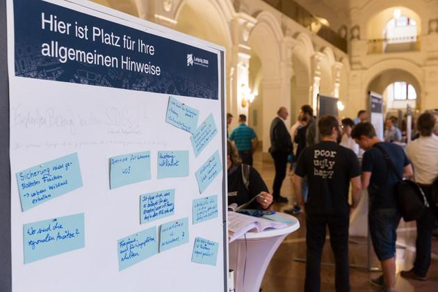 Eine Tafel mit blauen Zetteln, auf denen die Bürger Hinweise notiert haben. Im Hintergrund einige Menschen an Tischen und Ausstellungstafeln