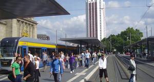 Menschen an der Straßenbahnhaltestelle am Leipziger Hauptbahnhof. Auf den Gleisen fährt eine Straßenbahn. Im Hintergrund ist das Wintergartenhochhaus.