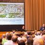 Eine Frau und ein Mann mit Mikrofon in der Hand stehen vor einem Publikum. Im Hintergrund eine Leinwand, auf der die Präsentation zum Stadtentwicklungskonzept präsentiert wird.