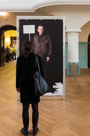 Eine Frau steht vor einem schwarzen Ausstellungsbanner mit einer Frau drauf.