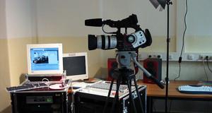 Eine Videokamera mit einem Scheinwerfer vor einem Mischpult und einem Video-Schnitt-Rechner