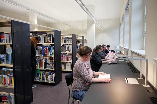 Langes Tischband unter der Fensterfront mit Arbeitsplätzen und Leselampen, Personen sitzen und arbeiten