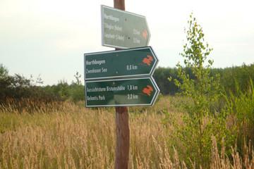 Bild wird vergrößert: Wegweiser für Wanderungen an einem Holzpfahl. Auf den Schildern ist ein Hase zu sehen und Entfernungsangaben.