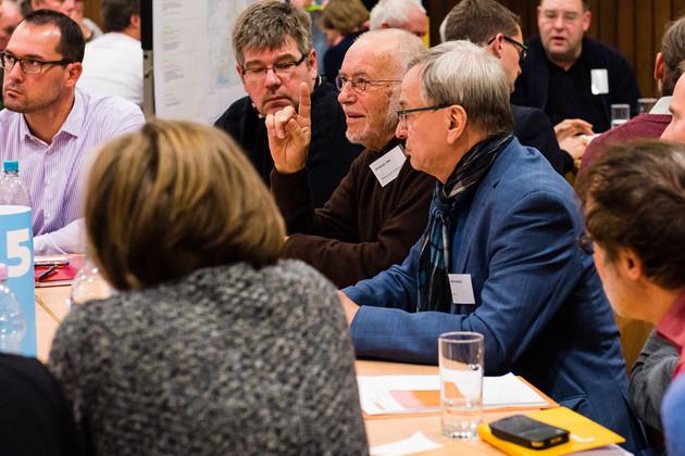 Blick auf drei Menschen, die am Tisch sitzen und diskutieren