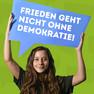 """Ein Mädchen hat sich mit dem Statement """"Frieden geht nicht ohne Demokratie"""", welches auf einer blauen Sprechblase steht, fotografieren lassen."""