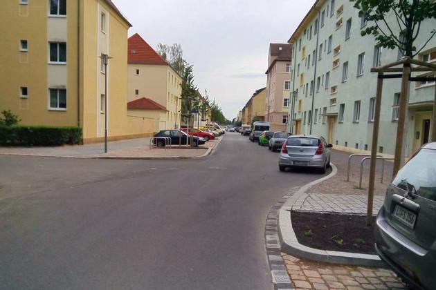Sanierte Demmeringstraße mit Häusern und parkenden Autos