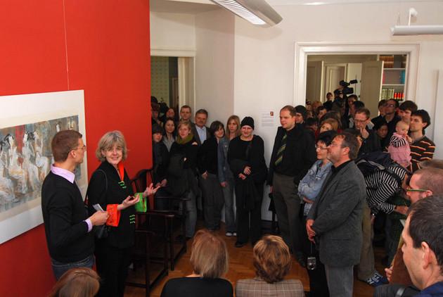 links im Bild sind Thomas Rötting und Dr. Gabriele Goldfuß vor einer roten Wand im Konfuzius Institut zu sehen, sie sprechen zu den zahlreichen stehenden Gästen des Tags der offenen Tür.