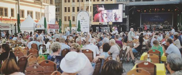 Zuschauer bei den Classic Open auf dem Leipziger Markt sitzen an Tischen und schauen Richtung Bühne