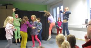Kinder spielen Zirkus in einem Kulturhaus. Sie hüpfen und haben rote Clownsnasen aufgesetzt.