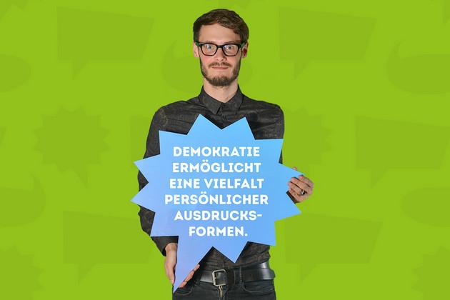 """Ein Mann hat sich mit dem Statement """"Demokratie ermöglicht eine Vielfalt persönlicher Ausdrucksformen."""" auf einer blauen Sprechblase fotografieren lassen."""