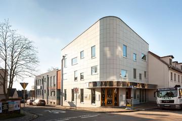 Bild wird vergrößert: Gebäude das Soziokulturellen Zentrums Anker. Eckgebäude an einer kleinen Straßenkreuzung, verkleidet mit großflächigen weißen Platten.