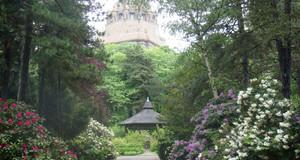 Südfriedhof mit hohen Bäumen und blühenden Rhododenronbüschen mit Blick auf das Völkerschlachtdenkmal