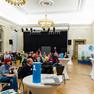 Im Festsaal der Kantschule sitzen etwa 60 Menschen in Kleingruppen und hören der Rede von Frau Dubrau zu.