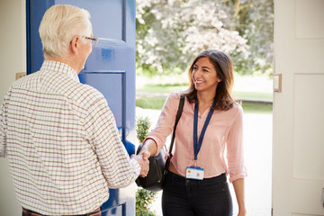 Bild wird vergrößert: Eine Frau begrüßt einen älteren Herren an seiner Haustür mit Handschlag.