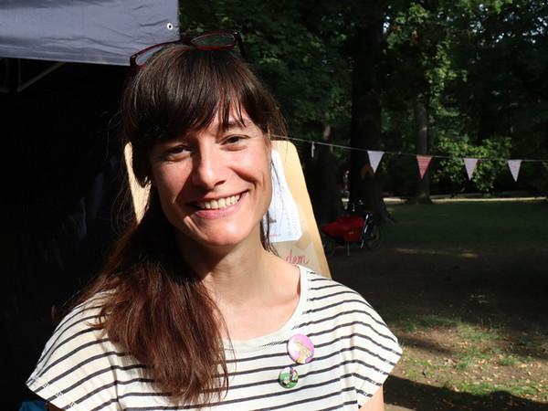 Eine junge Frau mit langen braunen Haaren steht im Grünen und lächelt ins Bild.