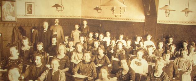Klassenfoto einer Mädchenklasse mit Lehrern im Klassenzimmer, um 1925