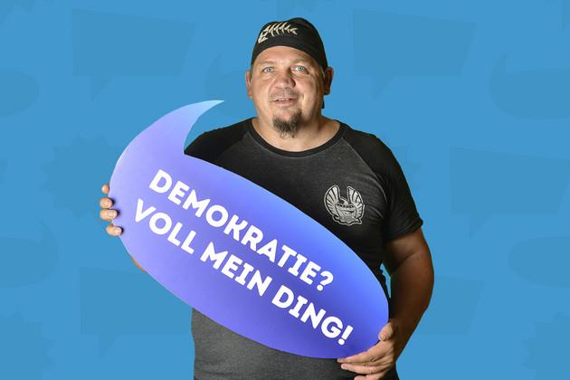 """Ein Mann hat sich mit dem Statement """"Demokratie? Voll mein Ding!"""" auf einer blauen Sprechblase fotografieren lassen."""