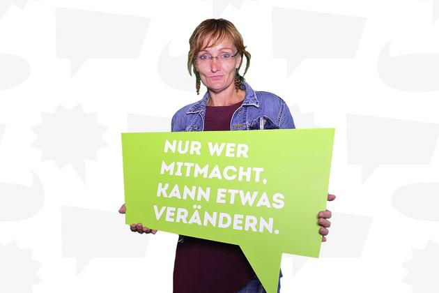 """Eine Frau hält eine Schild mit dem Statement """"Nur wer mitmacht, kann etwas verändern.""""."""
