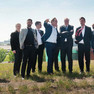 Eine Gruppe Männer und eine Frau stehen im Freien. In der Mitte steht Oberbürgermeister Jung und zeigt mit einer Hand in die Ferne.