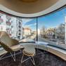 Innenansicht einer Wohnung mit Sitzecke vor einem großen gebogenen Fenster